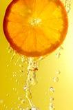 Gotitas de la naranja y de agua Foto de archivo libre de regalías