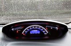 Gotitas del tablero de instrumentos y de la lluvia en el parabrisas del coche Imagenes de archivo