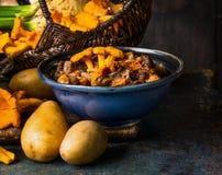 Gotować lasowe pieczarki w nieociosanym pucharze i gruli na ciemnym nieociosanym tle, frontowy widok Jesieni kucharstwo zdjęcie stock