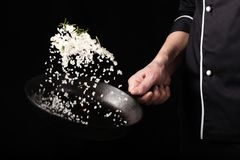 Gotować piec aromatyczną sól w niecce szef kuchni ręką Horyzontalny fotografia widok Ciemnego czerni tło z odbitkowym teksta tere obraz royalty free