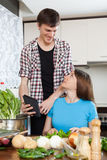 Gotować z elektroniczną książką w kuchni Obrazy Stock