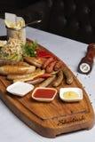Gotowane kiełbasy, ser z smażącymi pomidorami, pietruszka i wiśnia w restauracji, zdjęcia stock