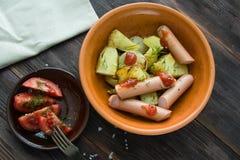 Gotowane kiełbasy z bocznym naczyniem piec grule i świeży Tom Obrazy Stock