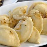 Gotowane kluchy z cebulami na białym talerzu towarzyszący zdobycza kurczaka kuchni kartoteki karmowej włoskiej fotografii poczta  obrazy royalty free