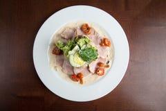 Gotowani jajka z uwędzonym baleronem i warzywami na bielu talerzu fotografia royalty free