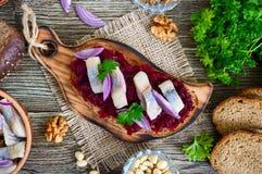 Gotowani kraciaści buraki, kawałki śledź, czerwone cebule, dokrętki na całym zbożowym chlebie zdjęcia stock