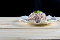 Gotowani ryż w bielu talerzu na drewno stole Obrazy Stock