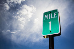 Gotta start somewhere. 1 Mile sign against a brilliant blue sky Royalty Free Stock Image