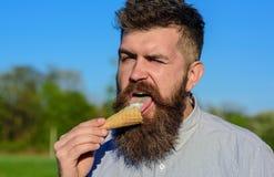 Gottegrisbegrepp Skäggig man med glasskotten Mannen med det långa skägget slickar glass Man med skägget och mustasch Royaltyfri Foto
