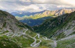 Gotthard mountain pass, Switzerland. Old road with tight serpentines on the southern side of the St. Gotthard pass bridging swiss alps at sunset in Switzerland Royalty Free Stock Image