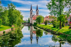 KOČEVJE - Slovenija. Gottschee and the Church of St. Bartholomew Rinža the river and the bridge by the reflection of the church and the trees in the water Stock Photo