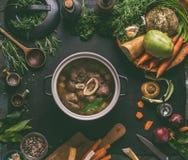 Gotująca wołowiny mięsna goleń z kością w kucharstwo garnku na ciemnym kuchennego stołu tle z niskimi carb warzywami i pikantność obraz royalty free