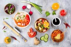 Gotujący asortowane jarzynowe sałatki i azjatykciego naczynie na kamiennym tle, zdjęcie stock