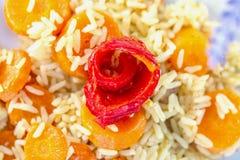 Gotujący biali ryż z marchewkami i czerwień smażyli słodkiego pieprzu obraz royalty free