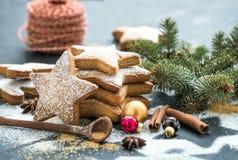 Gotujący Bożenarodzeniowi wakacyjni tradycyjni piernikowi ciastka z cukieru proszkiem, anyżem i cynamonowymi kijami na czerni, obraz stock