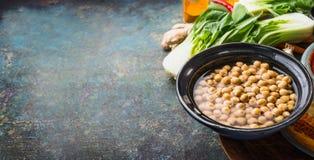 Gotujący Chickpeas w pucharze z jarskimi kulinarnymi składnikami na nieociosanym tle, miejsce dla teksta, sztandar Zdrowy jedzeni fotografia royalty free