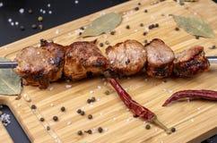 Gotujący grill na skewer jest na desce kropiącej z chili pieprzem, czarnym pieprzem i solą, obraz royalty free