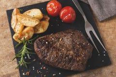 Gotujący grill wołowiny stek z smażącymi pomidorami i grulami obrazy royalty free