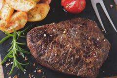 Gotujący grill wołowiny stek z smażącymi pomidorami i grulami fotografia royalty free