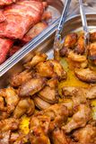 Gotujący kurczaków skrzydła i kuchenni tongs fotografia royalty free