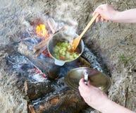 Gotujący na ognisku przy pinkinem, jedzenie przygotowywał w garnku na drewnie, grulach i pomidorach, zdrowy jarski jedzenie, kobi Fotografia Stock