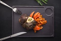 Gotujący osso buco stek z piec na grillu dzwonkowym pieprzem na kamień desce na czarnym tle zdjęcie royalty free