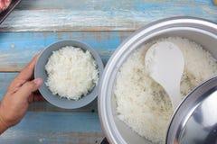 Gotujący ryż na plastikowej kopyści w elektrycznej ryżowej kuchence Obrazy Stock