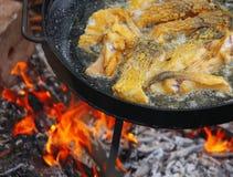 Gotujący się w oleju na rozpieczętowanym ogieniu, smaży rybi polędwicowego Obraz Stock