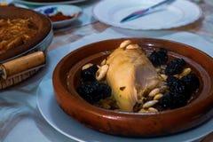 Gotuj?cy kurczak z przycina, migda?y, cebule i kropi z sezamem, Maroka?ski tagine obraz royalty free