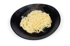 Gotuj?cy spaghetti makaron na czarnym naczyniu na bia?ym tle zdjęcie royalty free