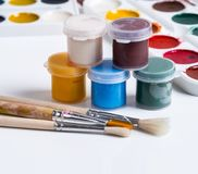 Gouache in jars, brushes and watercolors on a white background Royalty Free Stock Photos
