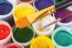 Gouache colors in cans and paintbrushes Stock Image