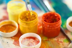 Gouache of different colors and paint brushes royalty free stock image