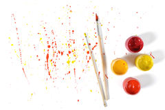Gouache jars and paint brushes on a white background with colorful spray in top view Royalty Free Stock Photo