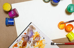 Gouache and paint brushes lie on paper. Royalty Free Stock Images