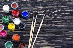 Gouache paints and brushes on wooden backgound Royalty Free Stock Images