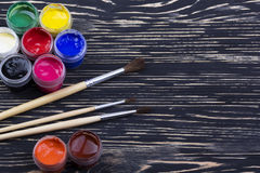 Gouache paints and brushes on wooden backgound Royalty Free Stock Photos