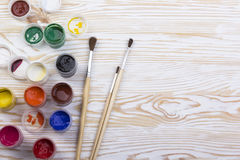 Gouache paints and brushes on wooden backgound Stock Photos