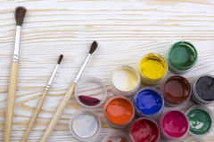 Gouache paints and brushes on wooden backgound Royalty Free Stock Photo