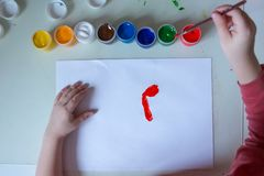 Gouache and water for painting and kid drawing on white paper.child doing artwork.the child dipped his brush in the stock image