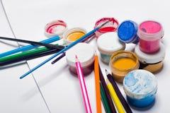Gouachefarbe, Bürsten und farbige Bleistifte auf einem hellen Hintergrund Stockfotografie