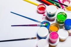 Gouachefarbe, Bürsten und farbige Bleistifte auf einem hellen Hintergrund Stockfotos