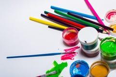 Gouachefarbe, Bürsten und farbige Bleistifte auf einem hellen Hintergrund Lizenzfreies Stockbild