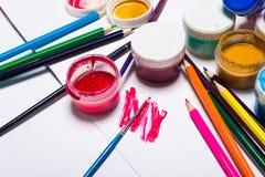 Gouachefarbe, Bürsten und farbige Bleistifte auf einem hellen Hintergrund Lizenzfreie Stockbilder
