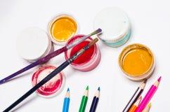 Gouachefarbe, Bürsten und farbige Bleistifte auf einem hellen Hintergrund Stockbild