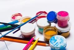 Gouachefarbe, Bürsten und farbige Bleistifte auf einem hellen Hintergrund Lizenzfreie Stockfotografie