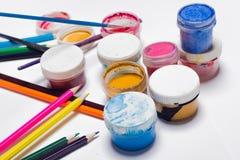 Gouachefarbe, Bürsten und farbige Bleistifte auf einem hellen Hintergrund Stockbilder