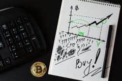 Goud bitcoin, een deel van toetsenbord en verbindend notitieboekje met diagram met het stijgen van digitale munt van bitcoin royalty-vrije stock afbeeldingen