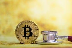 Goud bitcoin met stethoscoopcontrole omhoog van witte Gezondheidszorg als achtergrond royalty-vrije stock fotografie