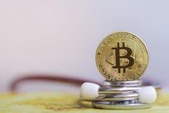 Goud bitcoin met stethoscoopcontrole omhoog van witte Gezondheidszorg als achtergrond stock afbeelding